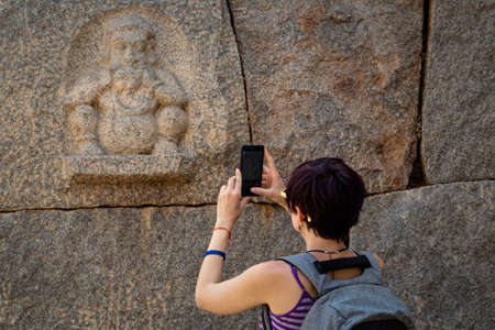 Girl tourist shoots a photo on a smartphone of an ancient bas-relief . The Group of Monuments at Hampi was the centre of the Hindu Vijayanagara Empire in Karnataka state in India