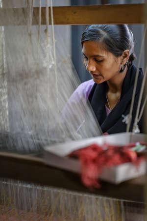 Ellora, Maharashtra, INDIA - JANUARY 15, 2018: Indian girl behind a traditional loom. Handmade traditional fabric Editorial