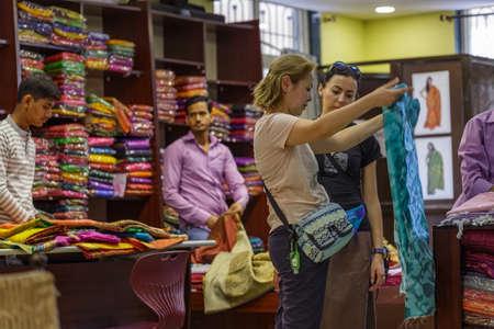 Ellora, Maharashtra, INDIA - JANUARY 15, 2018: European tourist girls in oriental traditional textile store. Girls buy a traditional scarf in the store