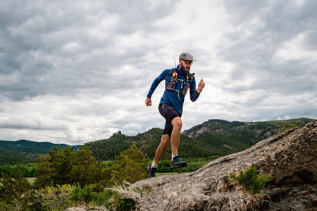 Runner runs in the rocky mountains. A man in a blue sweater and black shorts is training outdoors