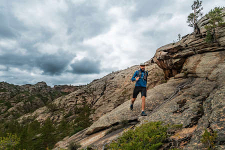 Runner runs on the rocky mountains. A man in blue jersey and black shorts is training outdoors Imagens