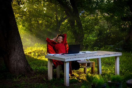 The girl works at a laptop in the garden in the summer. The work of a freelancer. Early morning outdoors Imagens