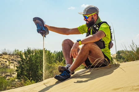Athlete runner pour out sand that ended up in his shoes. Trail running in desert. Young athlete in a yellow T-shirt and shorts sits on a sand dune