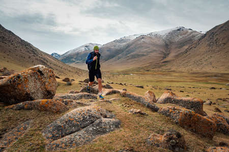 Male runner running on a mountain trail. Athlete runs in the mountains among the rocks. Man training in outdoors. Trail running