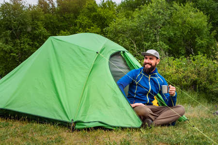 Joyful tourist at a campsite sitting near a green tent with a metal mug in his hands. Traveling in the summer