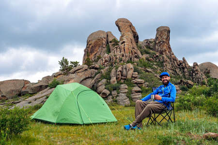 A joyful tourist in a campsite sits on a folding chair near a green tent with a metal mug in his hands. Camping overlooking unusual beautiful rocks. Traveling in the summer
