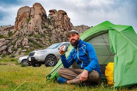 Tourist in a campsite sites near a green tent with a metal mug in his hands. Traveling in summer by car