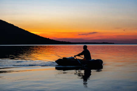 Fisherman in an inflatable boat floats on the lake. Silhouette on a sunset background. Imantau lake. Kazakhstan Imagens