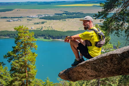 Athlete runner resting on the edge of a sticking cliff. Bearded athlete in shorts and a yellow T-shirt. View of the lake. Outdoor sports. Imantau lake. Kazakhstan