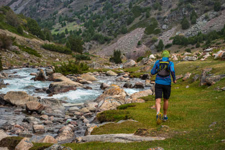 Runner guy is jogging in the highlands. Athlete runs near a mountain river. Man is training outdoors. Trail running