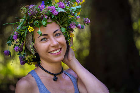 Summer portrait of a cute smiling girl in a wreath of flowers. Girl in the woods outdoors. Summer mood