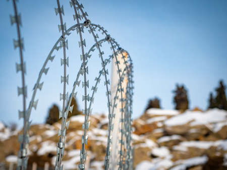 Security barrier with a barbed wire fence. Fence against the backdrop of snowy mountains Imagens