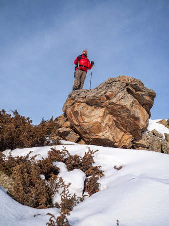 Hiker traveler with a backpack and in a red jacket in winter outdoors. A man stands on the edge of a large stone Imagens
