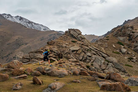 Athlete runs high in the mountains among the rocks. Bearded guy jogging in the mountains. Trail running Imagens
