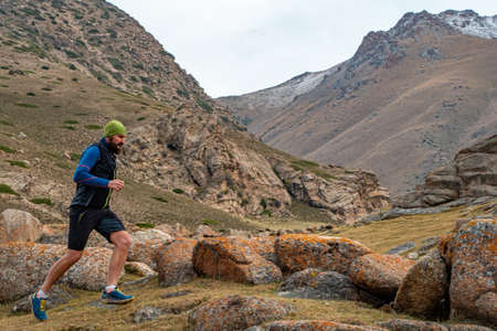 Bearded man athlete jogging outdoors in the mountains. Training high in the mountains. Sky running Imagens