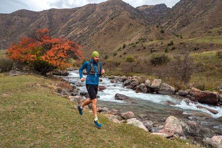 A guy jogs across a mountain river. Man training outdoors. Sky running