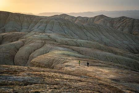 Travelers walk in the desert mountains in the evening. Altyn Emel National Park. Kazakhstan