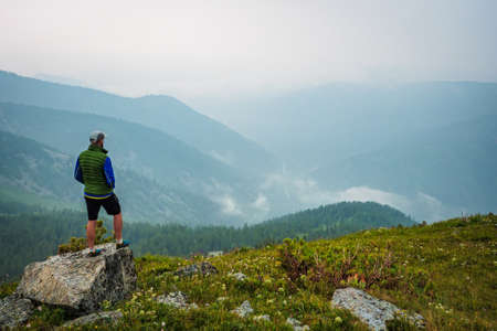 A man stands on a hill in front of a foggy mountain valley. Foggy weather high in the mountains in summer