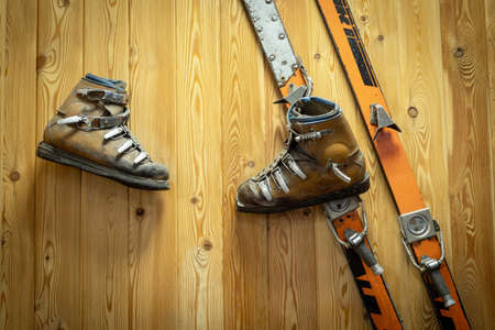 Vintage skiing and ski leather boots hang on a wooden wall. Sports equipment of the last century