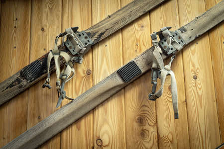 Vintage skiing hang on a wooden wall. Sports equipment of the last century Imagens