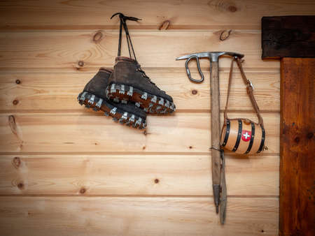 Vintage climbing leather boots and ice ax hang on a wooden wall. Antique Climbing Equipment