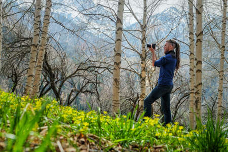 A man photographer stands on the trail in the spring birch forest. The guy holds a camera in his hand. View from the back. Fresh young grass and wildflowers. Alma-Ata's region. Kazakhstan.