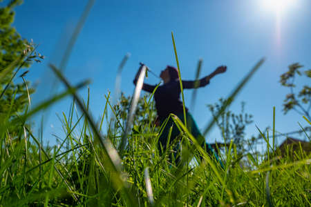 A girl plays badminton in a clearing. Summertime pastime. Focus on the foreground grass.