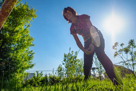 A girl plays badminton in a clearing. Summertime pastime Imagens