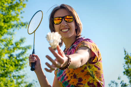 Portrait of a young woman playing badminton outdoors on a beautiful summer day