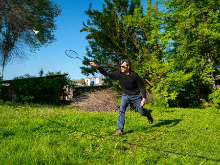 Guy play badminton outdoors on a beautiful summer day