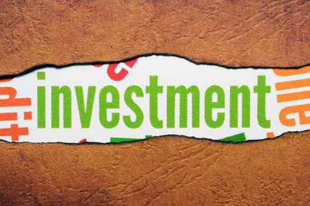 Investment text on torn paper photo