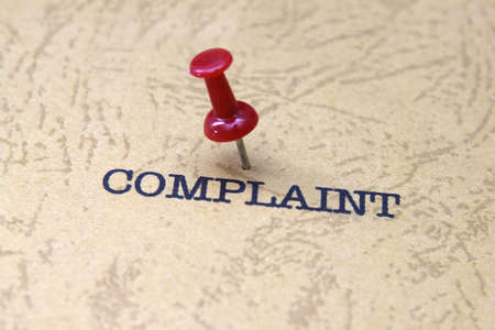 complain: Push pin on complaint text Stock Photo