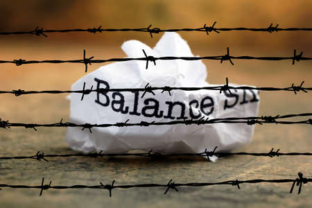 Balance crinkled paper against barbwire