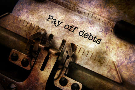 pay off: Pay off debts text on typewriter Stock Photo