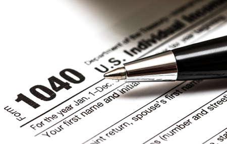 Formulario de impuestos US 1040 con bolígrafo y monedas Foto de archivo