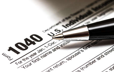 US 1040 tax form with pen, and coins Stock Photo