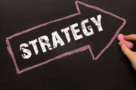 Strategy - female hand with chalk and arrow with text Stock Photo