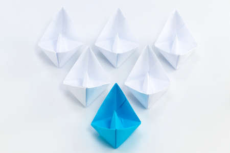 Leadership concept using blue paper ship among white.