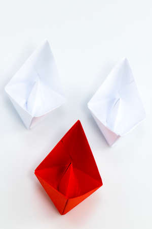 supervise: Leadership concept with red paper ship leading among white.