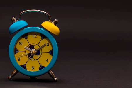 The Alarm clock on black background. Colored