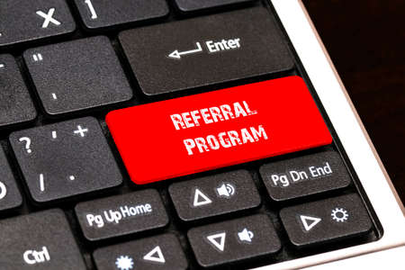 contracting: On the laptop keyboard the red button written Referral Program. Stock Photo