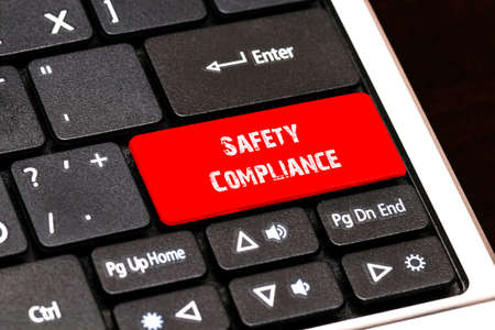 contracting: On the laptop keyboard the red button written Safety Compliance.
