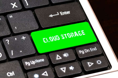 contracting: On the laptop keyboard the green button written CLOUD STORAGE. Stock Photo