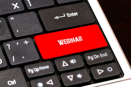 contracting: On the laptop keyboard the red button written Webinar.