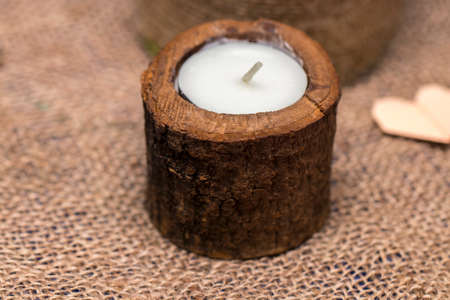 Candle in a wooden candlestick on a romantic background. Stock Photo