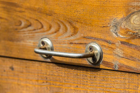 old wooden door with a handle in the background.
