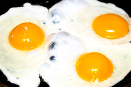 fryingpan: Fried eggs in a frying pan  for breakfast on a black background. Stock Photo