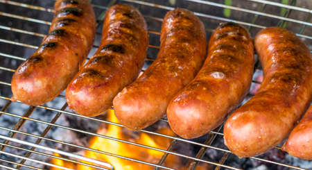 The Grilled sausage on the flaming grill