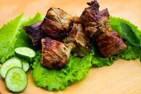 Pork shish kebab on a wooden table.
