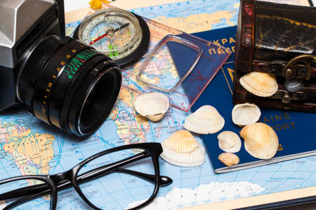 mapa conceptual: Pasaportes en un mapa del mundo.Cámara, gafas de sol y conchas marinas en el fondo